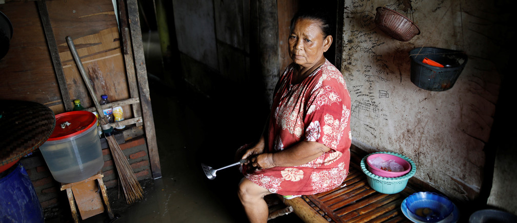 """Sainah sits in the kitchen area of her home, flooded by sea water, near Pantai Bahagia in Bekasi, West Java province, Indonesia, February 1, 2018. REUTERS/Darren Whiteside     SEARCH """"COASTLINE INDONESIA"""" FOR THIS STORY. SEARCH """"WIDER IMAGE"""" FOR ALL STORIES. - RC1D7CEF96E0"""