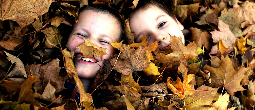Two Polish school boys play in a pile of leaves in a park in central Warsaw October 26, 2004. REUTERS/Peter Andrews Pictures of the Month October 2004  PA/ABP BEST QUALITY AVAILABLE - RTRE81Q