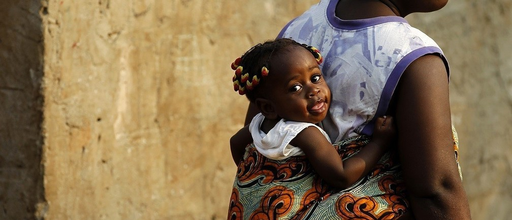 A woman with a baby on her back looks on at an informal settlement in the capital Luanda, August 30, 2012. Angolans will go to the polls on Friday to elect lawmakers and their president.