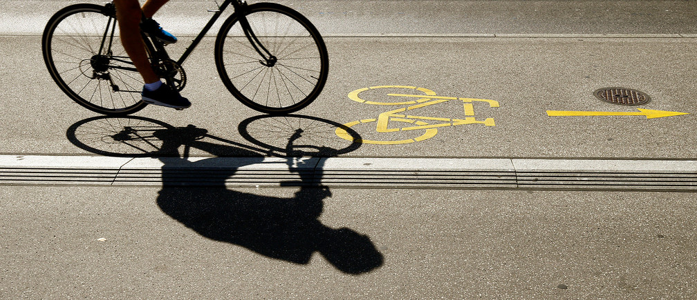 The silhouette of a cyclist is seen on a bike lane in Zurich, Switzerland August 29, 2017.  REUTERS/Arnd Wiegmann - RC149E55FC60