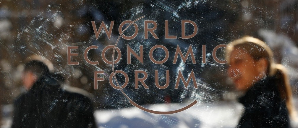 People are pictured through a plastic board as they leave the annual meeting of the World Economic Forum (WEF) in Davos, Switzerland