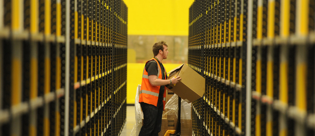 A worker lifts a box at Amazon's new fulfilment centre after it was opened by Scotland's First Minister Alex Salmond in Dunfermline, Scotland, November 15, 2011.The warehouse covers more than one million square feet (93,000 square metres), about the size of 14 soccer pitches, and is Amazon?s biggest in the United Kingdom. It will create 750 permanent jobs, along with a further 1,500 temporary jobs during peak periods.  REUTERS/Russell Cheyne (BRITAIN - Tags: POLITICS BUSINESS) - LM1E7BF17XX01