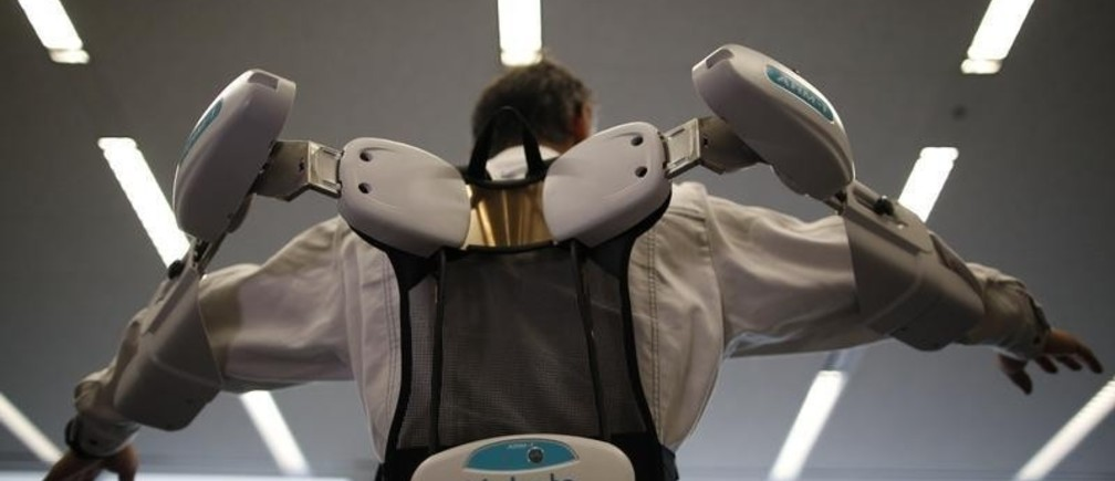 An employee of ActiveLink Co. established under the intrapreneurship of Panasonic Corp, demonstrates ARM01, called 'Raku Vest', jointly developed with Kubota Corp., in Tokyo June 2, 2014. The ARM01is a robotic exoskeleton developed to help farmers and construction workers. REUTERS/Issei Kato (JAPAN - Tags: SCIENCE TECHNOLOGY SOCIETY BUSINESS TPX IMAGES OF THE DAY) - RTR3RSJQ
