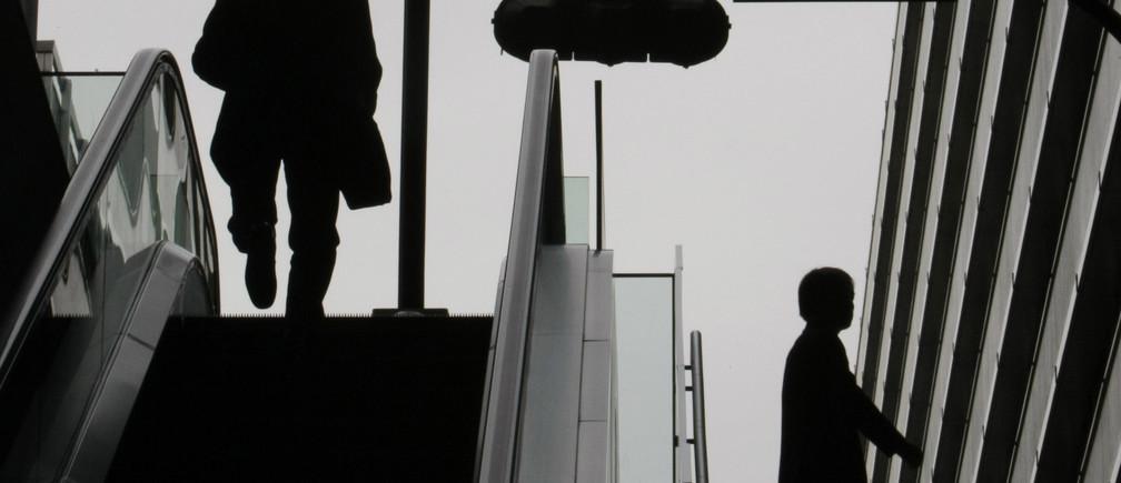 A man walks off an escalator in a business district of Tokyo November 10, 2008.    REUTERS/Kim Kyung-Hoon (JAPAN) - GM1E4BA106J01