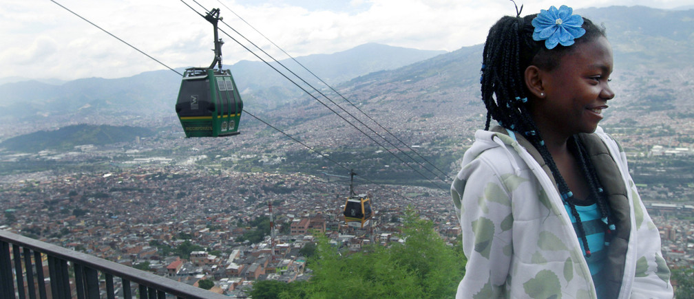 A girl stands nearby as cable cars pass behind her, at a viewpoint overlooking Medellin