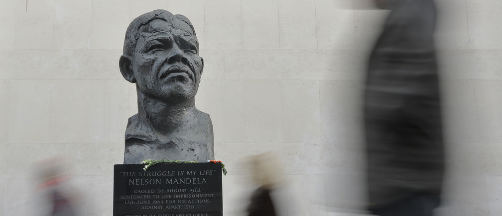 Passers-by look at a statue of former South African President Nelson Mandela on the South Bank in central London December 9, 2013. REUTERS/Toby Melville