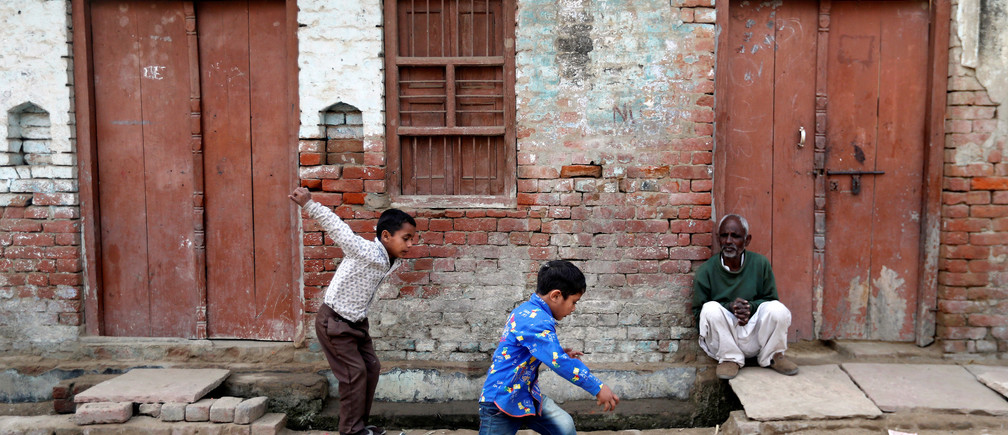 Children play as a man sits outside a house in Nayabans village in Bulandshahr district, Uttar Pradesh, India December 5, 2018. Picture taken December 5, 2018. REUTERS/Adnan Abidi   To match Insight INDIA-ELECTION/RELIGION - RC1C02C6B450