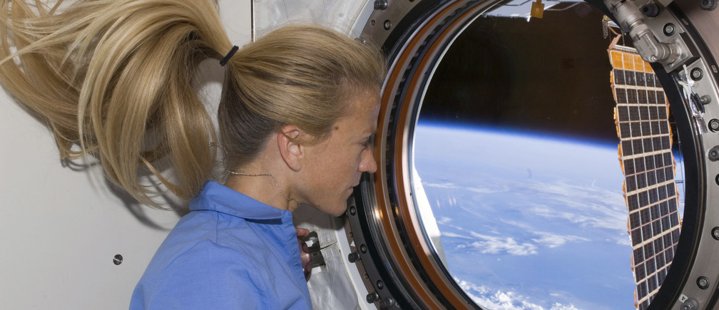 Astronaut Karen Nyberg looks through a window in the newly installed Kibo laboratory of the International Space Station while Space Shuttle Discovery is docked with the station in this photo released by NASA June 11, 2008