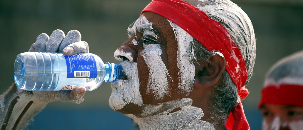 A traditonally dressed Australian Aboriginal performer has a drink of water as he prepares to participate in a 'Corroboree' showcasing traditional dance during an event to mark National Reconciliation Week on Sydney's Coogee Beach May 27, 2015.  REUTERS/David Gray - GF10000108521
