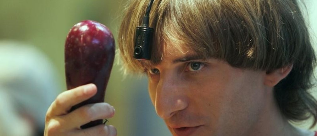 British cyborg musician and performer Neil Harbisson poses while holding an eggplant in Palma de Mallorca on the Spanish Balearic island of Mallorca September 9, 2011. Harbisson, who was born with achromatopsia, a condition that only allows him to see in black and white, became in 2004 the first person in the world to be fitted with an eyeborg. The eyeborg works with a head-mounted camera that picks up the colours in front of it and converts them in into sound waves. By memorising the frequencies related to each colour, Harbisson can perceive up to 36 colors.