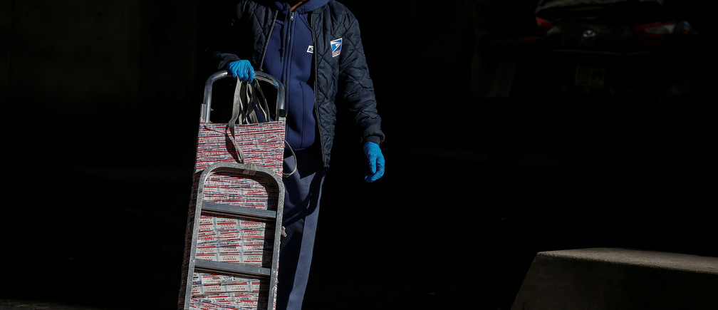 A U.S. Postal delivery person pushes a cart in the financial district in New York City, U.S., November 28, 2017. REUTERS/Brendan McDermid - RC191C34E9D0