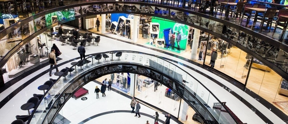 People walk through the Mall of Berlin shopping centre during its opening night in Berlin, September 24, 2014.