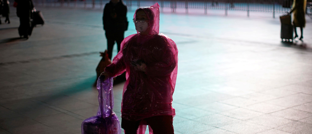 A woman wears a face mask and plastic raincoat as a protection from coronavirus at Shanghai railway station, in Shanghai, China February 17, 2020. REUTERS/Aly Song     TPX IMAGES OF THE DAY - RC2E2F9KBNMV