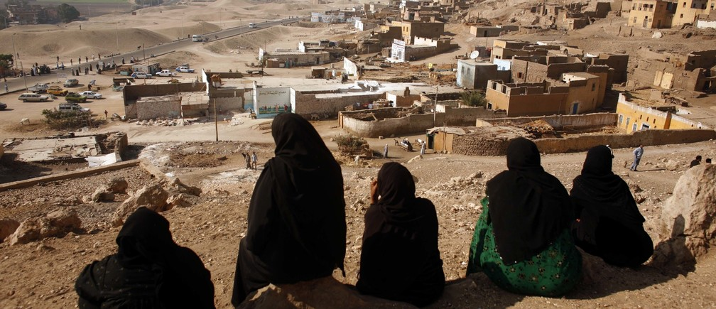 A group of women villagers watches from the hill-top as bulldozers move in to start demolishing the village of Gurna, built on top of ancient tombs near the southern city of Luxor December 2, 2006. Bulldozers moved in on Saturday to start demolishing Gurna, which lies on top of an ancient necropolis.    REUTERS/Goran Tomasevic (EGYPT) - GM1DUBNHXZAA