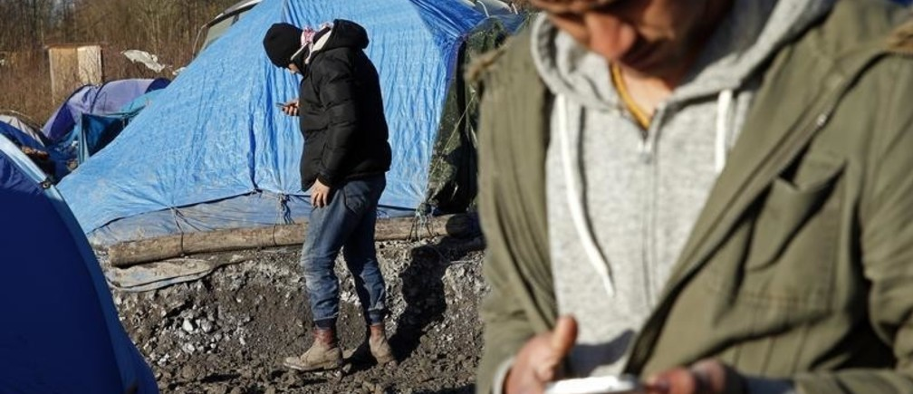 Migrants check their mobile phones next to shelters in a muddy field called the Grande-Synthe jungle, near Dunkirk, northern France, January 12, 2016. The Grande-Synthe jungle is a camp of tents and makeshift shelters where migrants and asylum seekers from Irak, Kurdistan and Syria gather.   REUTERS/Benoit Tessier - LR2EC1C16N29E