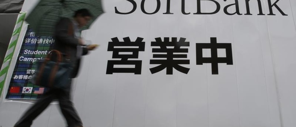 "A man holding an umbrella walks past the logo of Softbank Corp at its branch in Tokyo April 22, 2014. Softbank Corp CEO Masayoshi Son is lobbying sceptical Washington officials to let him buy a second U.S. mobile operator, saying he would help to break up a cozy U.S. wireless oligopoly. Son says he is an outsider who stirred up a price battle that benefited consumers after he took over Vodafone's failing Japanese operation eight years ago. The word in 2nd row reads ""opening"". Picture taken April 22, 2014. REUTERS/Yuya Shino (JAPAN - Tags: BUSINESS TELECOMS) - GM1EA4O02E701"