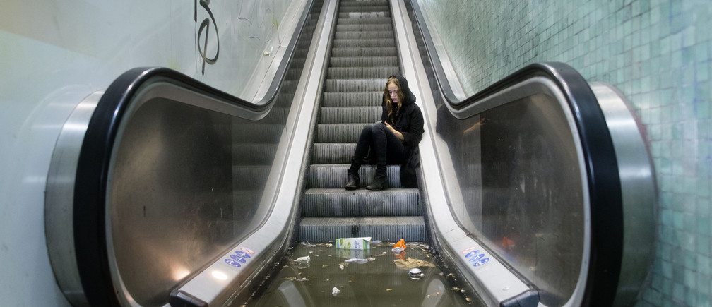A woman calls for assistance after being trapped by water at a flooded train station during a heavy rainstorm in Copenhagen.
