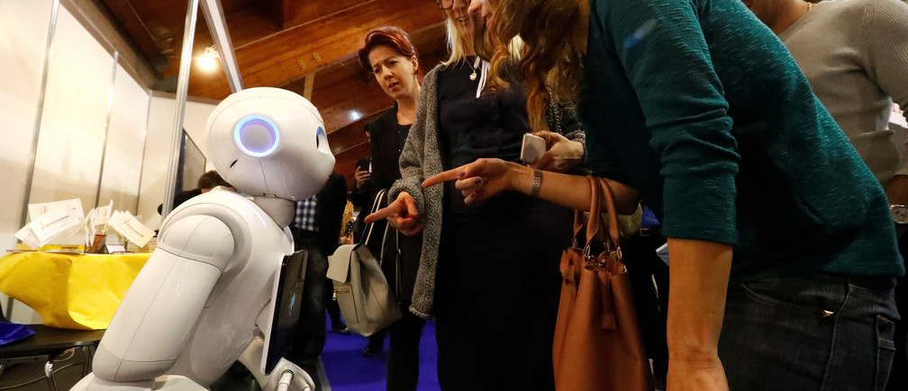 Women communicate with the humanoid robot Pepper during Riga Comm 2017, a business technology and innovation fair in Riga, Latvia November 9, 2017. REUTERS/Ints Kalnins - RC1E49CBBB70