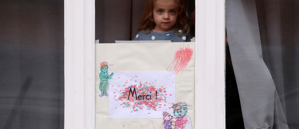 Four year old Belgian girl Ida stands behind her drawing, in honor of the rescuers, inside her house after Belgian government imposed a coronavirus lockdown in an attempt to slow down the coronavirus disease (COVID-19), in Brussels, Belgium March 19, 2020.  REUTERS/Yves Herman - RC27NF9GODUF