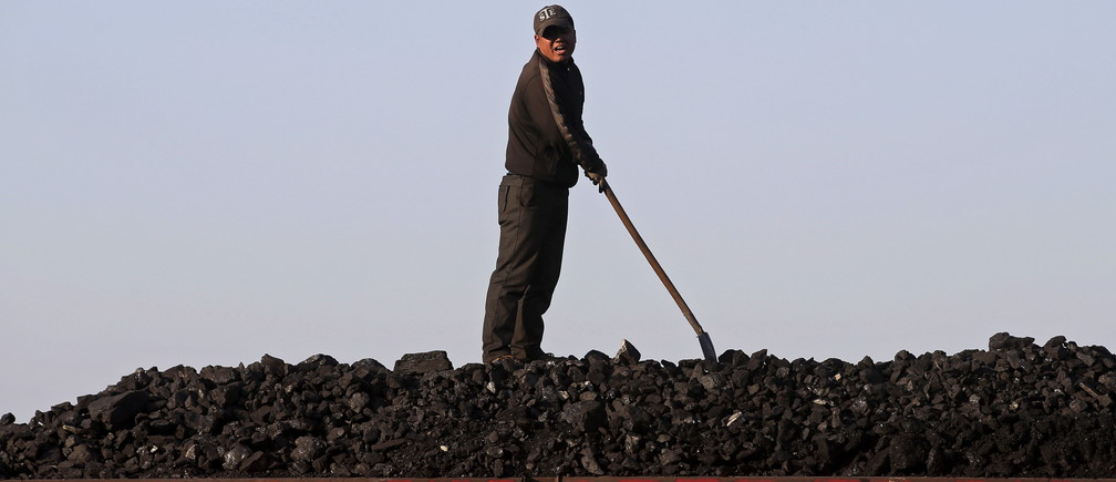 A worker speaks as he loads coal on a truck at a depot near a coal mine from the state-owned Longmay Group on the outskirts of Jixi, in Heilongjiang province, China, October 24, 2015. To match story CHINA-COAL/JIXI     Picture taken on October 24, 2015. REUTERS/Jason Lee - GF20000045461