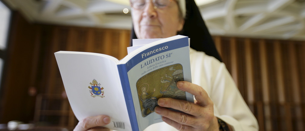 """A nun reads Pope Francis' new encyclical titled 'Laudato si' at the Vatican June 18, 2015. Pope Francis demanded swift action on Thursday to save the planet from environmental ruin, urging world leaders to hear """"the cry of the earth and the cry of the poor"""", plunging the Catholic Church into political controversy over climate change. In the first papal document dedicated to the environment, he calls for """"decisive action, here and now,"""" to stop environmental degradation and global warming, squarely backing scientists who say it is mostly man-made. REUTERS/Max Rossi TPX IMAGES OF THE DAY      - GF10000131581"""