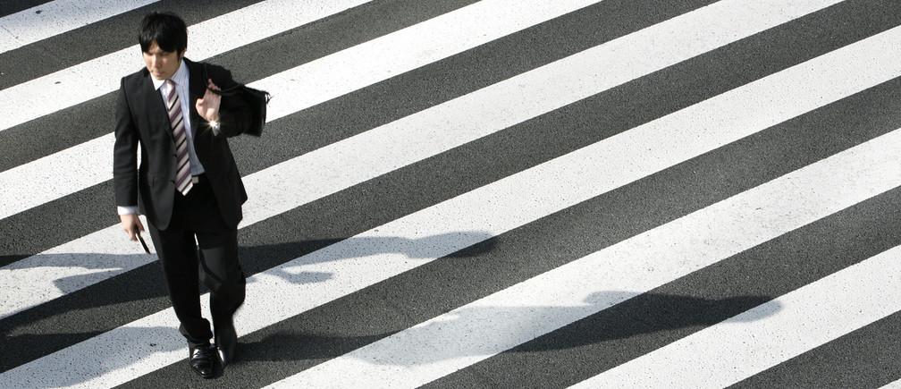 A man crosses a street in Tokyo August 3, 2009.   REUTERS/Stringer (JAPAN BUSINESS EMPLOYMENT) - GM1E58J0VUT01