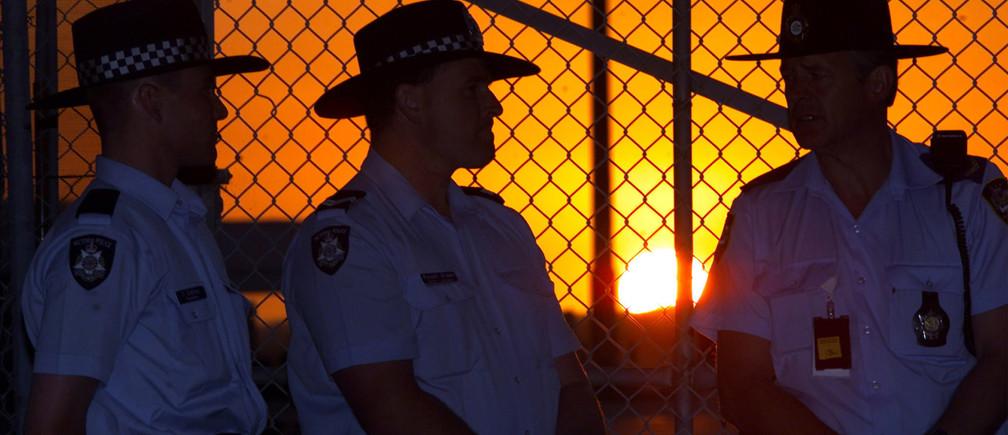 Australian Protective Service guards are silhouetted as the sun sets at Tullamarine Airport before the arrival of alleged Nazi mass murderer Konrad Kalejs on January 7. Kalejs, a Lativian-born Australian citizen, returned to Australia in the wake of a storm surrounding his alleged leadership of a Nazi death squad in World War II, a claim the 86-year-old has always denied.WB/CC - RP2DRICYMJAA