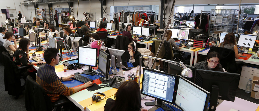 Employees work in front of their computers at the Vente-Privee.com company's headquarters in Saint-Denis near Paris October 24, 2013. REUTERS/Charles Platiau   (FRANCE - Tags: BUSINESS) - RTX14MDG