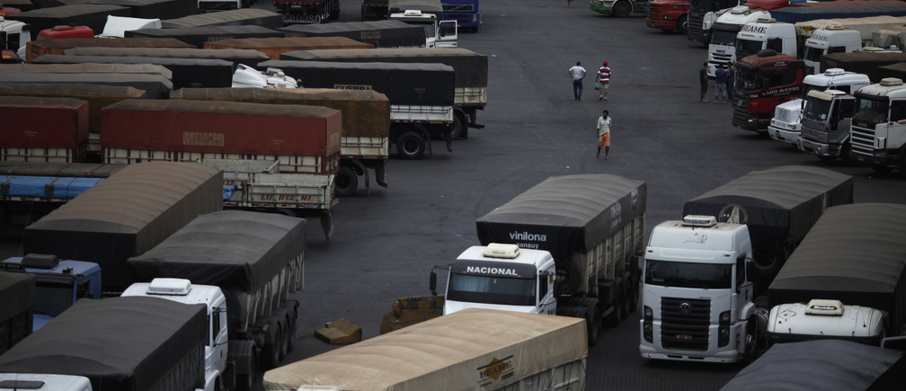 Drivers walk in front of trucks parked as they wait to unload their cereal grain freight at Ecopatio in Cubatao, September 20, 2012.