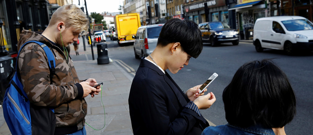 Pedestrians look at their phones near Brick Lane in London.