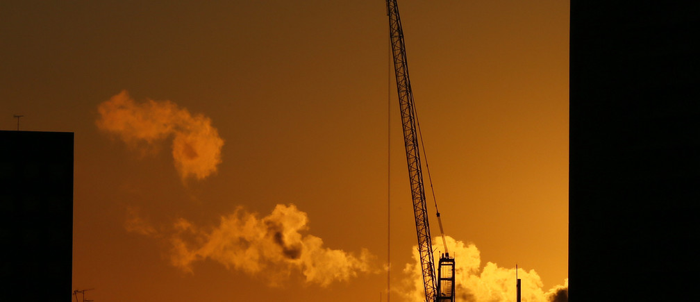 A crane is silhouetted during sunrise in central London
