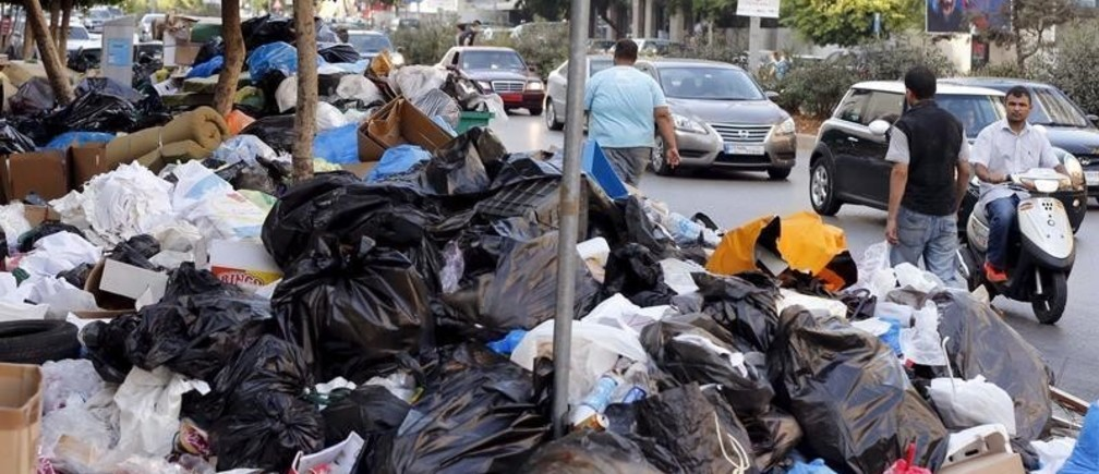 A man on a scooter, pedestrians and cars pass by garbage piled up along a street in Beirut, Lebanon August 26, 2015. The powerful Shi'ite party Hezbollah and its Christian allies walked out of an emergency Lebanese cabinet meeting on Tuesday in protest at a proposed solution to a garbage disposal crisis that has ignited violent protests in Beirut. Public anger that has come to a head over the trash crisis turned violent at the weekend, with scores of protesters and security forces injured. REUTERS/Mohamed Azakir  - RTX1PRW2