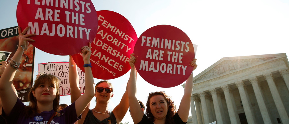 Demonstrators hold signs outside the U.S. Supreme Court as the court is due to issue its first major abortion ruling since 2007 against a backdrop of unremitting divisions among Americans on the issue and a decades-long decline in the rate at which women terminate pregnancies in Washington, U.S. June 27, 2016. REUTERS/Kevin Lamarque - D1AETMHXRXAB