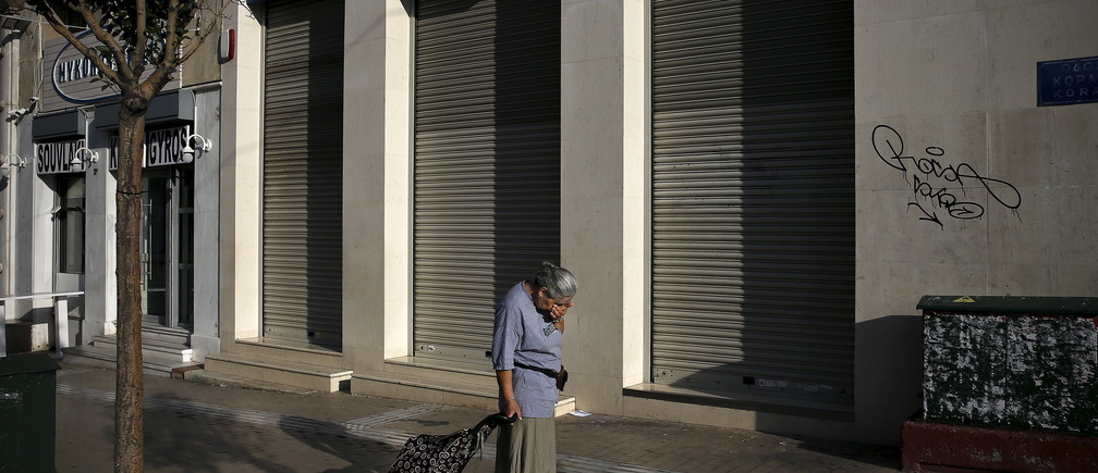 A woman pulling a shopping cart reacts outside a closed Eurobank branch in Athens, Greece June 29, 2015. Greece closed its banks and imposed capital controls on Sunday to check the growing strains on its crippled financial system, bringing the prospect of being forced out of the euro into plain sight.   REUTERS/Alkis Konstantinidis      TPX IMAGES OF THE DAY      - GF10000143182