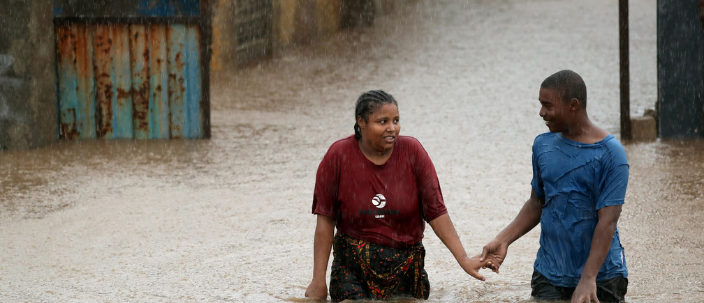 A man helps a woman through a flooded neighbourhood in the aftermath of Cyclone Kenneth, in Pemba, Mozambique, April 28, 2019. REUTERS/Mike Hutchings  TPX IMAGES OF THE DAY - RC1672267310