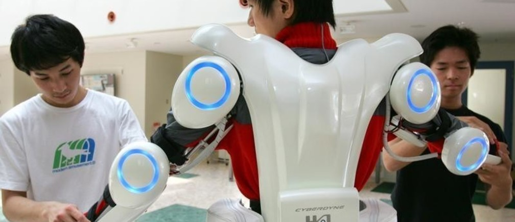 """Graduate school students assist to wear the robot suit """"Hybrid Assistive Limb (HAL) 5"""", developed by professor Yoshiyuki Sankai at Tsukuba Industrial Liaison Cooporation Research Center of University of Tsukuba, northeast of Tokyo June 24, 2005. The robotic suit can give an average man twice his usual strength and looks like a sleek, high-tech suit of white armour or perhaps equipment for American football players of the future. The gadget was developed to assist the elderly in their everyday lives. Picture taken June 24, 2005. To match feature Tech-Japan-Robots. REUTERS/Kimimasa Mayama  KM/JJ - RP6DRMRQCWAB"""