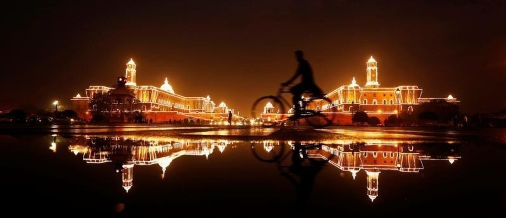 A cyclist rides past the Illuminated Indian Defence Ministry (L), Presidential Palace (C) and Home Ministry ahead of India's Independence Day celebrations in New Delhi, India, August 13, 2016. REUTERS/Adnan Abidi  - S1AETVFPPCAA