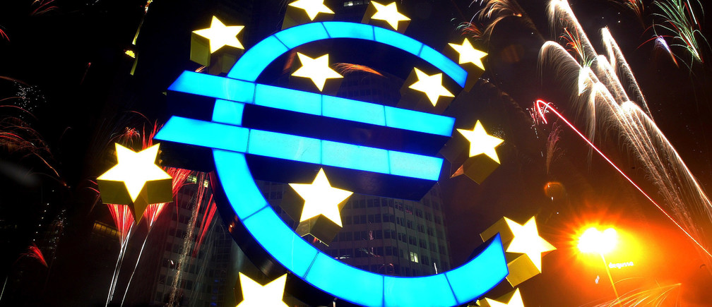 Fireworks illuminate the sky around a huge euro sculpture, designed by German artist Ottmar Hoerl, in front of the headquarters of the European Central Bank (ECB) in Frankfurt, January 1, 2002. Several thousand people in Frankfurt celebrated at a party on the streets around the ECB to welcome Europe's new currency, the euro. UNICS REUTERS/Kai Pfaffenbach REUTERS  KP - RP3DRIFSZXAA