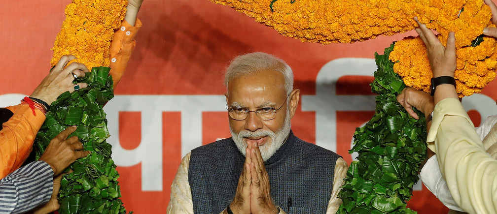 Indian Prime Minister Narendra Modi gestures as he is presented with a garland by Bharatiya Janata Party (BJP) leaders after the election results in New Delhi, India, May 23, 2019. REUTERS/Adnan Abidi     TPX IMAGES OF THE DAY - RC1BBC590B00