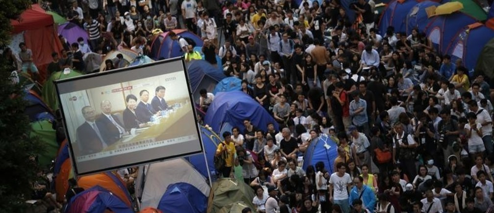 """Pro-democracy protesters watch formal talks between student protest leaders and government officials on a video screen near the government headquarters in Hong Kong October 21, 2014. Hong Kong Chief Executive Leung Chun-ying said on Tuesday there was room for the committee that selects candidates for the territory's 2017 election to be made """"more democratic."""" REUTERS/Carlos Barria (CHINA - Tags: CIVIL UNREST POLITICS TPX IMAGES OF THE DAY) - GM1EAAL1O7201"""