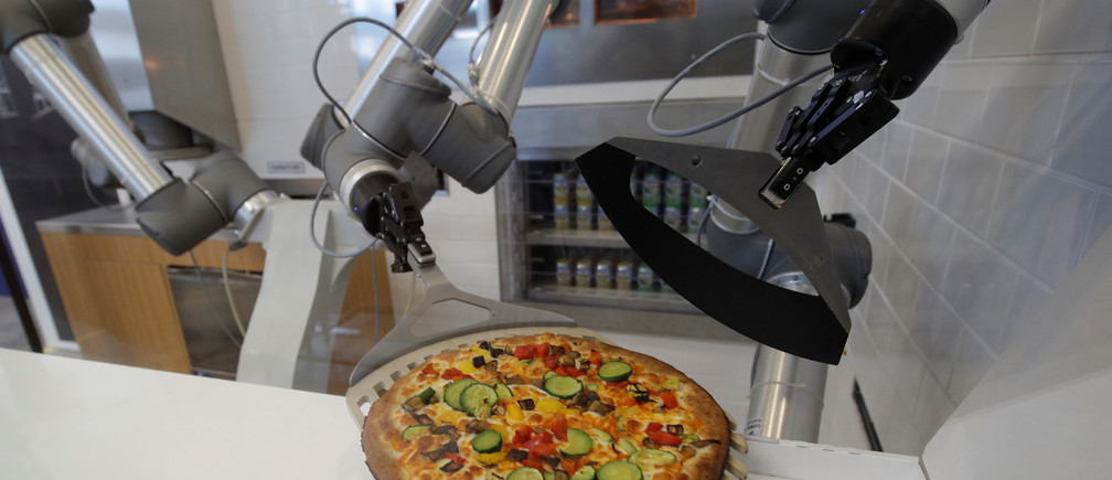A pizzaiolo robot prepares a pizza before the customer's eyes at the showroom of French food startup EKIM in Montevrain near Paris, France, June 26, 2018. Picture taken June 26, 2018.  REUTERS/Philippe Wojazer - RC12FDFA79A0
