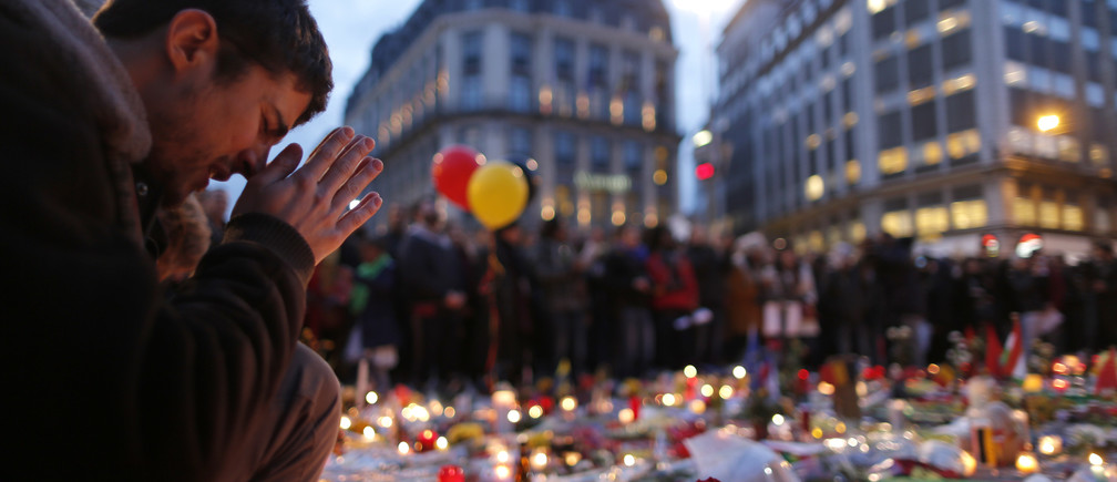 A man attends a memorial gathering near the old stock exchange in Brussels.