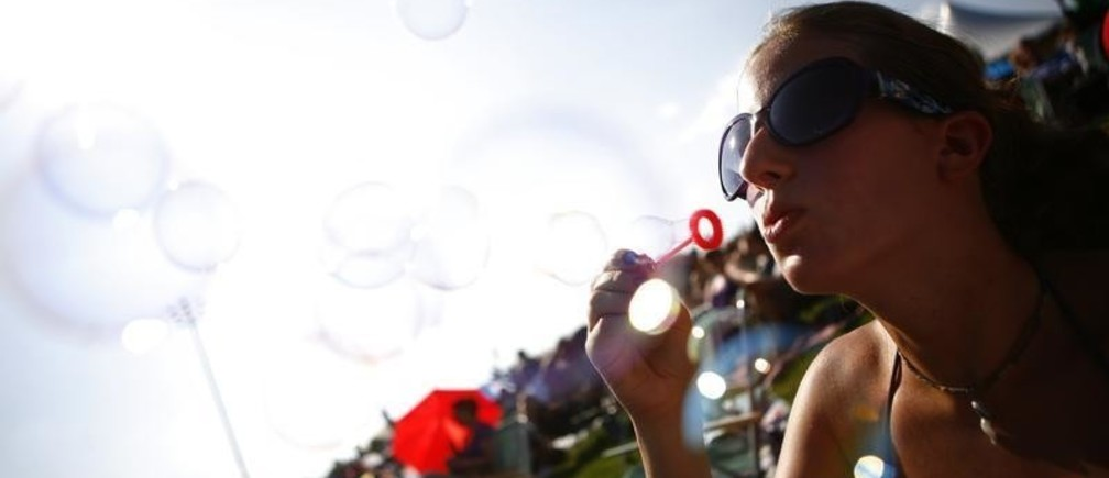 A woman blows bubbles while waiting for the start of the Bethel Woods Music Festival near the site of the original Woodstock Music Festival in Bethel, New York August 15, 2009. The concert, featuring a handful of the original bands, was held to commemorate the 40th anniversary of the festival. REUTERS/Eric Thayer (UNITED STATES ENTERTAINMENT SOCIETY) - GM1E58G0GNF01
