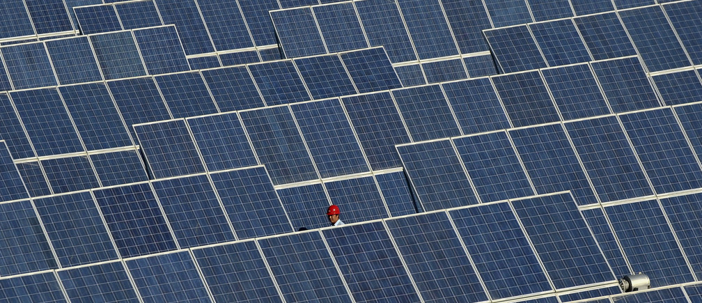 An employee walks between rows of solar panels at a solar power plant on the outskirts of Dunhuang, Gansu province June 10, 2011. REUTERS/Stringer (CHINA - Tags: ENERGY ENVIRONMENT SCI TECH) - GM1E76A10N901