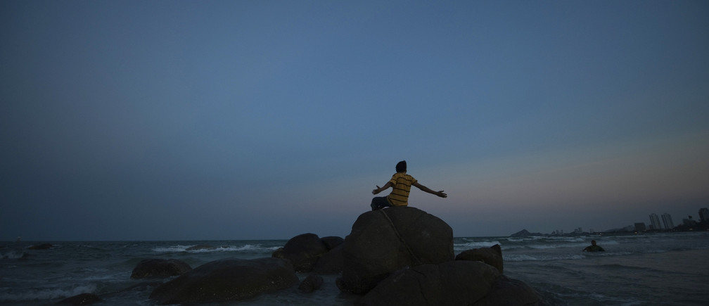 A man sits on a boulder at the seaside in the Thai resort city of Hua Hin, about 200 km (125 miles) south of Bangkok February 26, 2009. Hua Hin is the host for the 14th ASEAN summit, scheduled to be held in Thailand's Prachuap Khiri Khan province from February 27 to March 1, 2009.     REUTERS/Adrees Latif  (THAILAND) - GM1E52R03AJ01