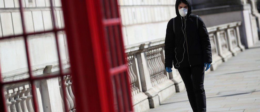A woman wearing a protective face mask and gloves walks through Westminster as the spread of the coronavirus disease (COVID-19) continues, London, Britain, March 24, 2020. REUTERS/Hannah McKay