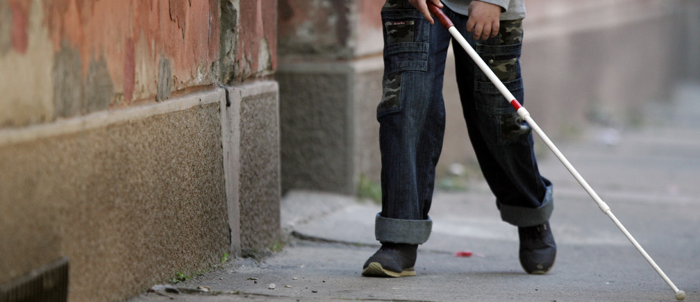 """A blind boy walks with a white stick on World Sight Day in Belgrade October 12, 2006. World Sight Day is a global annual event, held under the auspices of """"VISION 2020: The Right to Sight,"""" a joint initiative of the World Health Organization and the International Agency for the Prevention of Blindness. REUTERS/Marko Djurica"""