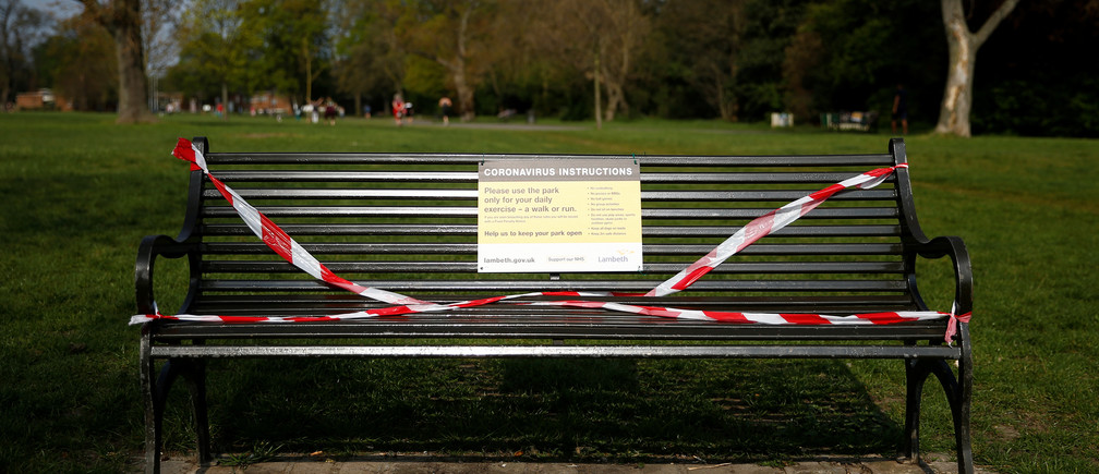 A taped off bench with a notice is seen in Brockwell Park in London as the spread of the coronavirus disease (COVID-19) continues, London, Britain, April 11, 2020. REUTERS/Henry Nicholls - RC292G92Y8MW
