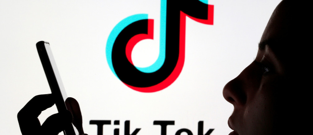 A person holds a smartphone as Tik Tok logo is displayed behind in this picture illustration taken November 7, 2019. Picture taken November 7, 2019. REUTERS/Dado Ruvic/Illustration - RC2V6D9ZIFU5