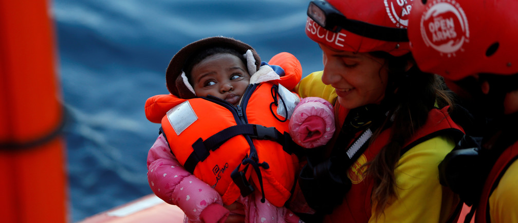 A search and rescue operation off the coast of Libya carries a migrant baby to safety